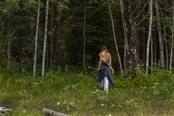 Rear view of woman walking in a forest with bow and arrow - TCF05789