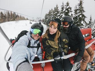 Italy, Modena, Cimone, portrait of happy friends in a ski lift - JPIF00001