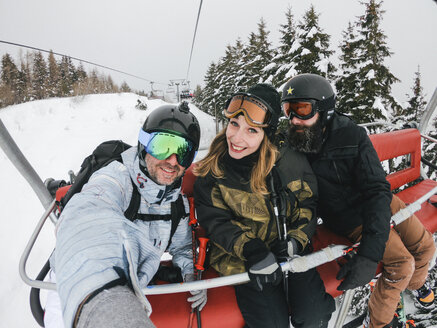 Italy, Modena, Cimone, portrait of happy friends in a ski lift - JPIF00001