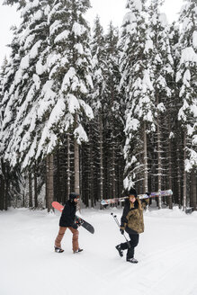 Italy, Modena, Cimone, couple with skiers and snowboard walking in winter forest - JPIF00010