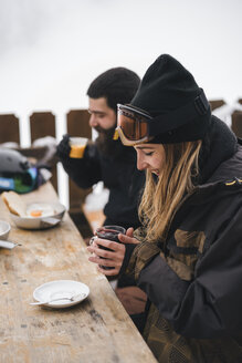 Couple in skiwear having a hot drink at mountain lodge - JPIF00013