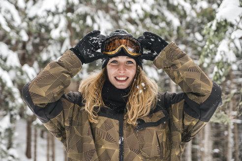 Portrait of happy young woman in skiwear in winter forest - JPIF00019