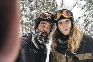 Selfie of happy couple in skiwear grimacing in winter forest - JPIF00025