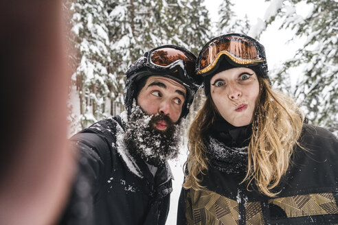 Selfie of happy couple in skiwear grimacing in winter forest - JPIF00025
