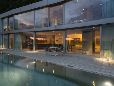 Switzerland, lighted modern villa at dusk with terrace and pool in the foreground - LAF02077