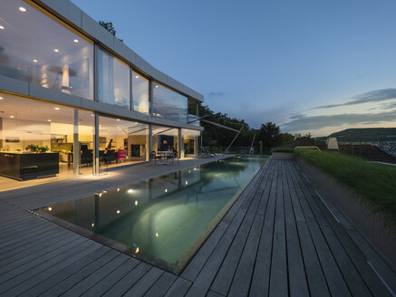 Switzerland, lighted modern villa at dusk with terrace and pool in the foreground - LAF02080