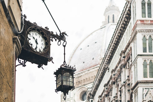 Italy, Florence, old clock and lantern at house front on winter - MGIF00206