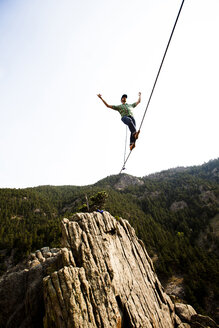 A male highliner walks the Elephant Buttresses highline in Boulder Canyon, Colorado. - AURF01972