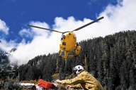 A helicopter prepares to land, picking up workers after a work in the field. - AURF01978