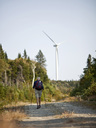 A man hikes along a trail with a wind turbine looming in the background. - AURF01999