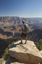 A man standing on a rock outcrop looking at the view of a desert canyon landscape. - AURF02002