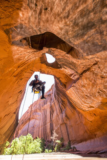 A man rapelling while canyoneering in a desert canyon. - AURF02017