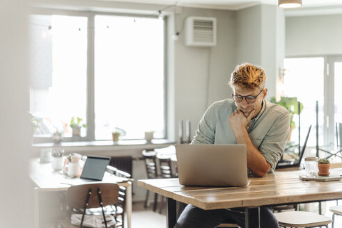 Young man sitting in coffee shop, using laptop - GUSF01243
