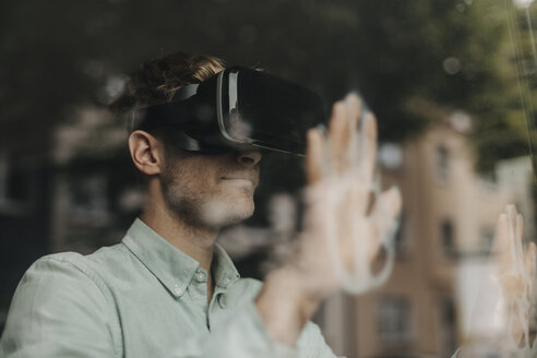 Young man standing at the window, using VR glasses - GUSF01258