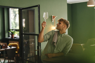 Young business owner checking wine glass in his restaurant - GUSF01282