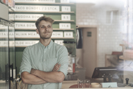 Young man working in his start-up cafe, portrait - GUSF01288