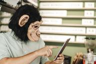 Man wearing monkey mask, using digital tablet - GUSF01291