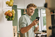 Young business owner drinking coffee, checking smartphone - GUSF01297