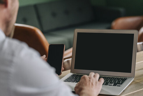 Man sitting at table, using laptop and smartphone - GUSF01300