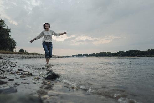 Laughing woman running at the riverside - KNSF04349