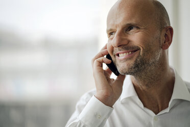 Smiling businessman standing in his office, talking on his mobile phone - KNSF04361