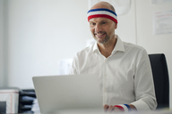 Businessman sitting in office, wearing sweat bands, using laptop - KNSF04367