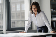 Businesswoman working in office, looking at blueprints - KNSF04376