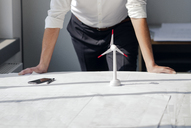 Engineer working in his office with model of a wing´d wheel on his desk - KNSF04379
