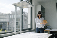 Woman holding architectural model of house, using VR glasses - KNSF04385
