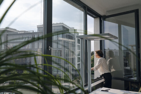 Businesswoman standing in office, looking out of window - KNSF04397