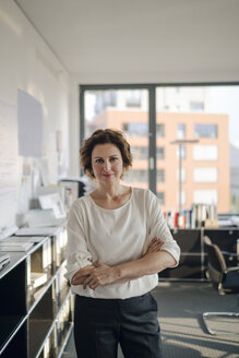 Successful businesswoman standing in her office with arms crossed - KNSF04400