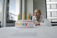 Businessman celebrating his birthday in the office, blowing out candles - KNSF04415