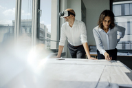 Two architects working on blueprints, man using VR glasses - KNSF04460
