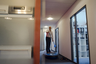 Businessman standing on paddle board, exercising in office corridor - KNSF04487