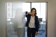 Successful businesswoman standing in office door, smiling - KNSF04490