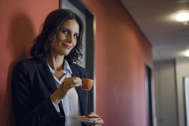 Mature businesswoman standing in office corridor, drinking coffee - KNSF04505