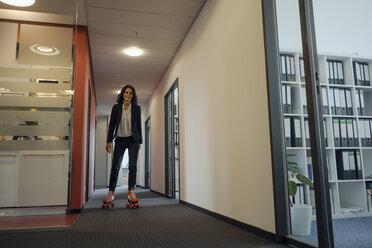 Mature businesswoman rollerskating in office corridor - KNSF04508