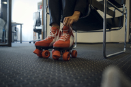 Mature businesswoman sitting in office, putting on roller skates - KNSF04511