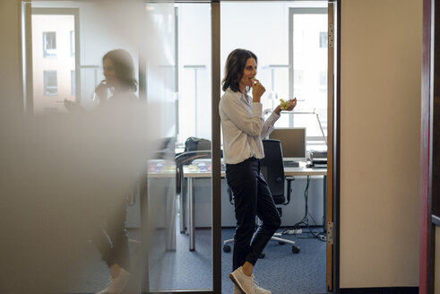Businesswoman standing in office, eating grapes - KNSF04514