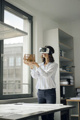 Woman holding architectural model of house, using VR glasses - KNSF04526
