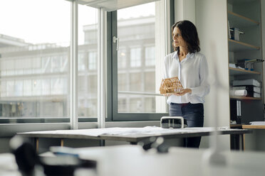 Businesswoman holding architectural model of a house - KNSF04529