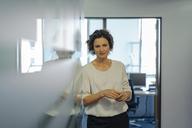 Shy businesswoman standing in office - KNSF04535