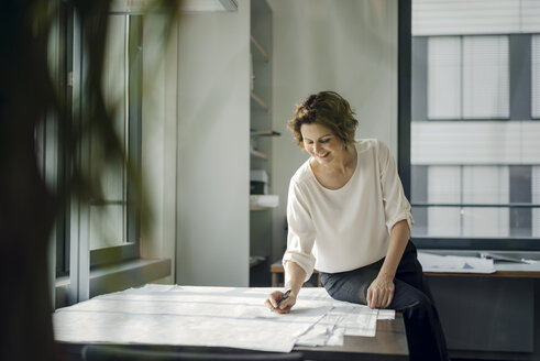 Businesswoman sitting in office, working on blueprints - KNSF04538