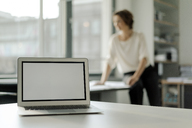 Laptop on shelf, businesswoman working in background - KNSF04544