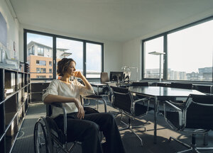 Disabled business woman sitting in wheelchair, smiling - KNSF04550