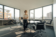 Successful businesswoman sitting on desk in her office with arms crossed - KNSF04553