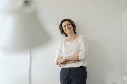 Businesswoman leaning against wall in office, with arms crossed, smiling - KNSF04556
