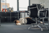 Tired businesswoman sleeping on floor under her desk - KNSF04562