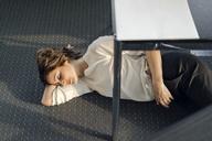 Tired businesswoman sleeping on floor under her desk - KNSF04565