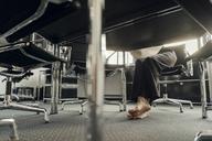 Bare feet of businesswoman under her desk - KNSF04568